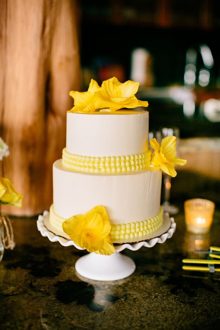 "A few gladiolus and yellow fondant beads accented the simple two-tier buttercream cake. ""I went with fresh flowers because I loved the element of realness they added,"" Charita says."