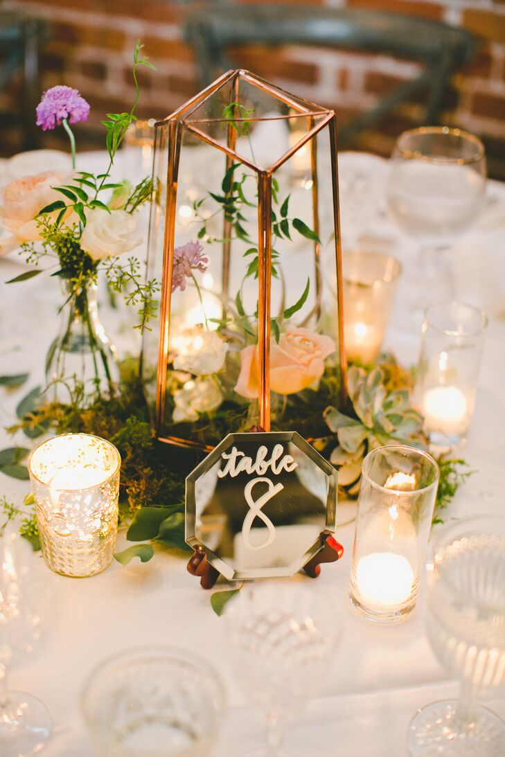 Tables were set with glowing votive candles, gold-caged hurricane vases and moss set inside terrariums. Apothecary jars and vintage bud vessels were also mixed in on tabletops.