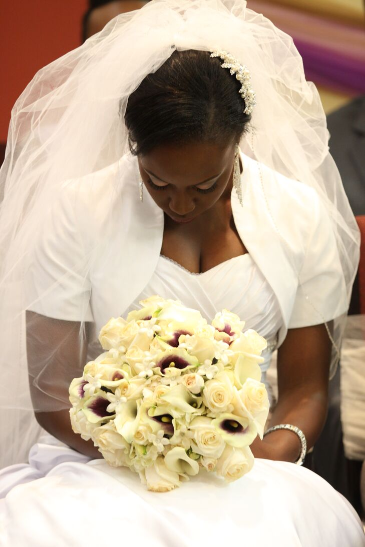 During the classic white wedding ceremony, Mayowa covered her bare shoulders with an elegant bolero for sophisticated modesty. She also wore a billowing tulle veil pinned into her curled updo.