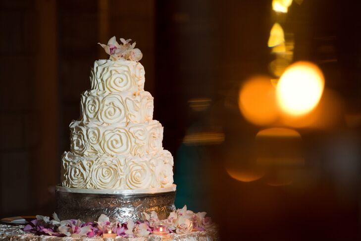 The couple chose a four-tier confection baked by The Sugar Monkey for their wedding day. It was decorated with rosette details and topped with a white orchid.