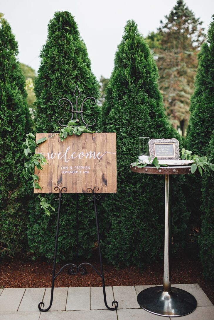 To introduce guests to the evening's whimsical rustic theme, Yan and Stephen incorporated a number of handcrafted touches throughout the decor. The couple had a wooden welcome sign featuring playful calligraphy specially made for the ceremony entrance, which Sweet Annie Floral Design decorated with wispy wines for a fresh feel.