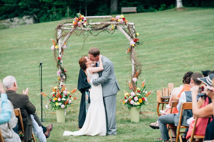 Olivia and Ben hosted their Unitarian ceremony on the lawn, where they exchanged vows under a rustic birch arch draped in bright, seasonal flowers and boughs of curly willow.
