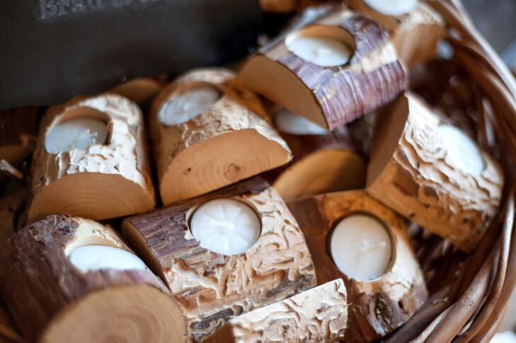 Guests took home white tea light candles as their wedding favors, which were placed inside wood holders. The wood was hand-carved into the shape of the holder, which was cut from juniper branches.