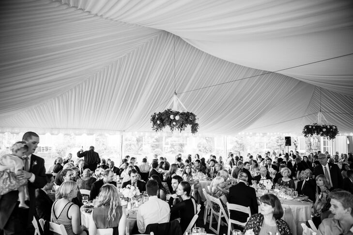 The reception took place under the white tent set up on the lawn at Alderbrook Resort and Spa in Union, Washington. Elegant chandeliers covered in leafy greens hung from the ceiling, bringing the surrounding landscape in for the celebration.