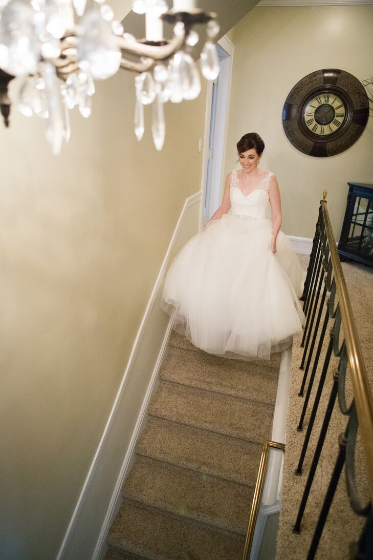Elena walked down the staircase wearing her white A-line wedding dress designed by Allure Bridals, with sheer lace straps attached to the sweetheart neckline and lace-accented bodice. The rest of the gown flared out into a full tulle ball gown skirt.