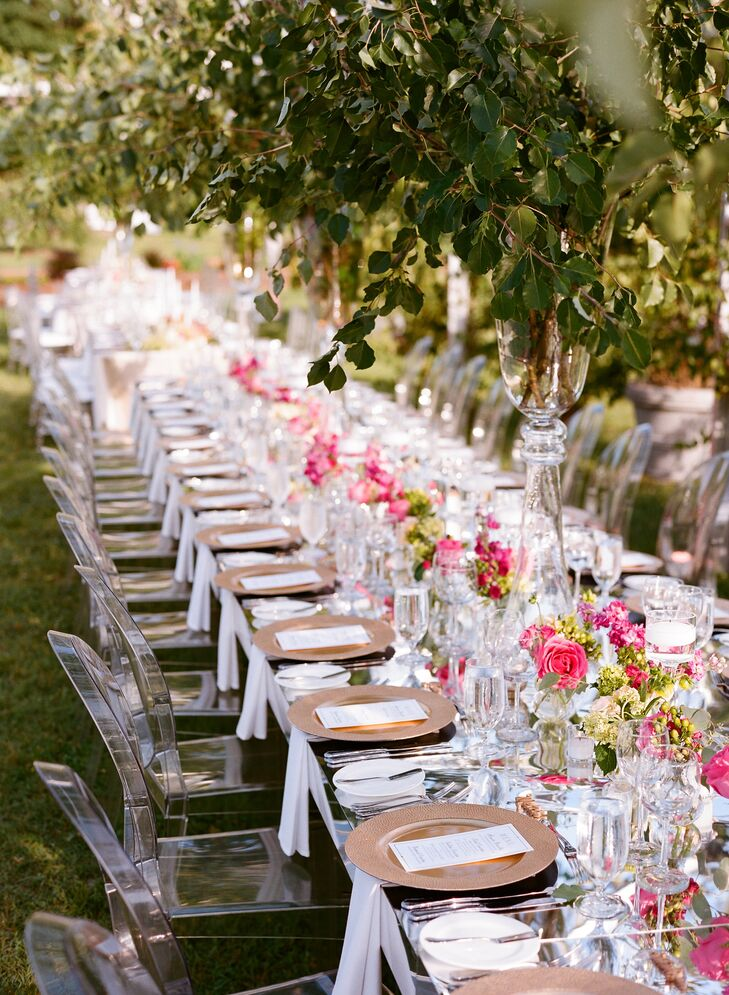 Long tables were decorated with hot-pink peonies, garden roses, stock and hypericum. Greenery hung from the tent frame along with chandeliers.