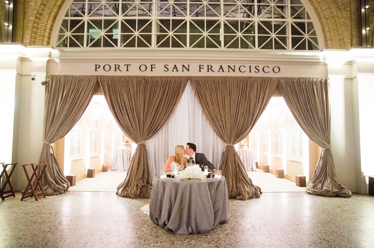 Courtney and Patrick shared a romantic kiss while they sat at the sweetheart table, covered with clean gray linens and decorated with white flower arrangements on the front.