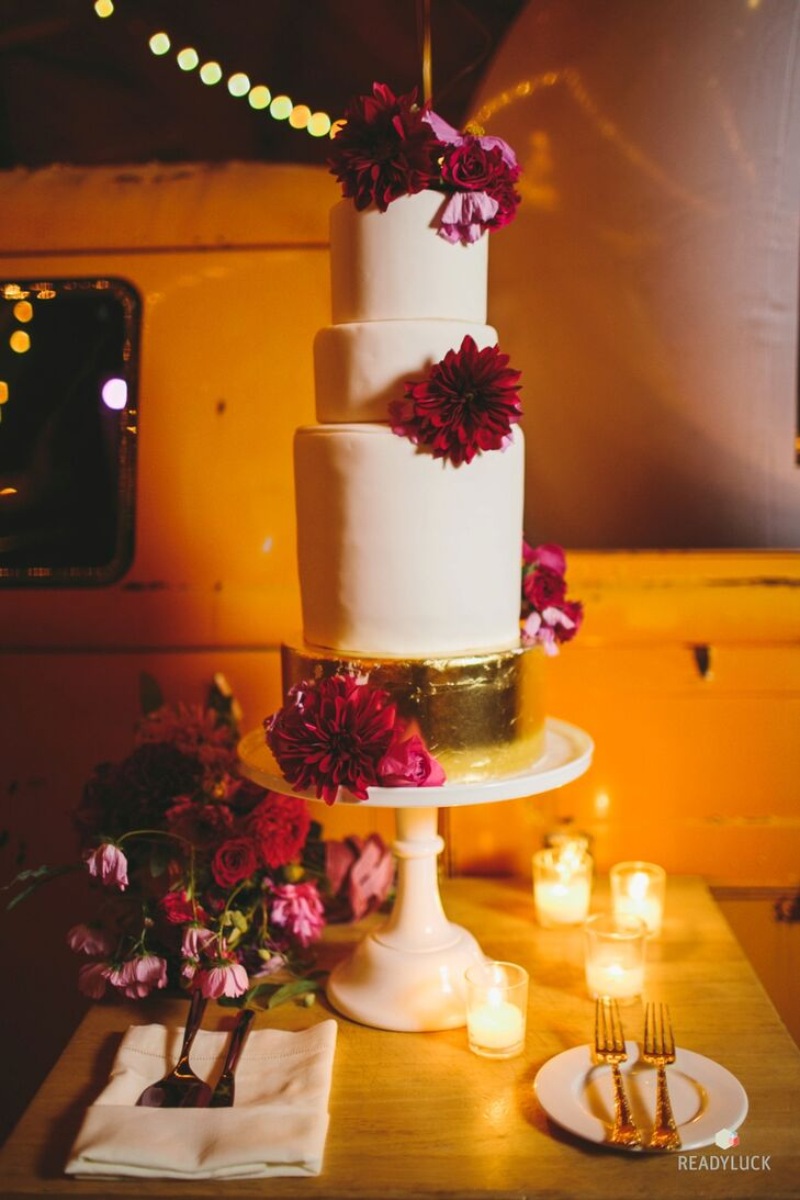 A four-tier cake with a gold foundation was adorned with berry red-colored dahlias.