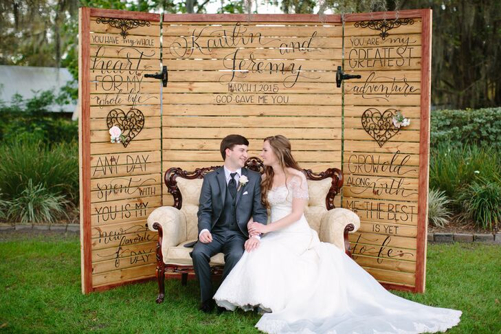 A family friend built this wall, which was used as a backdrop for reception photos. Another friend handwrote favorite quotes, and the couple found the antique love seat at a consignment store.