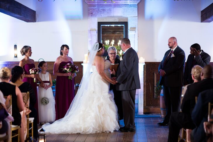 The couple stood with hands held at the altar in front of guests during their ceremony.