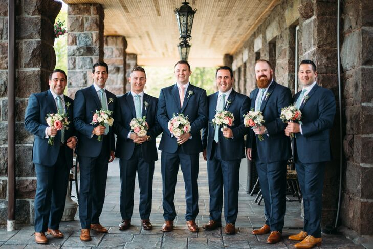 From the start, Jon knew that he wanted his groomsmen in tailored navy suits with brown shoes. The sartorial decision, as well as the waterfront locale, set the tone for the rest of the decor, leading Katherine to select a color palette of navy blue, sage green, peach and gold.