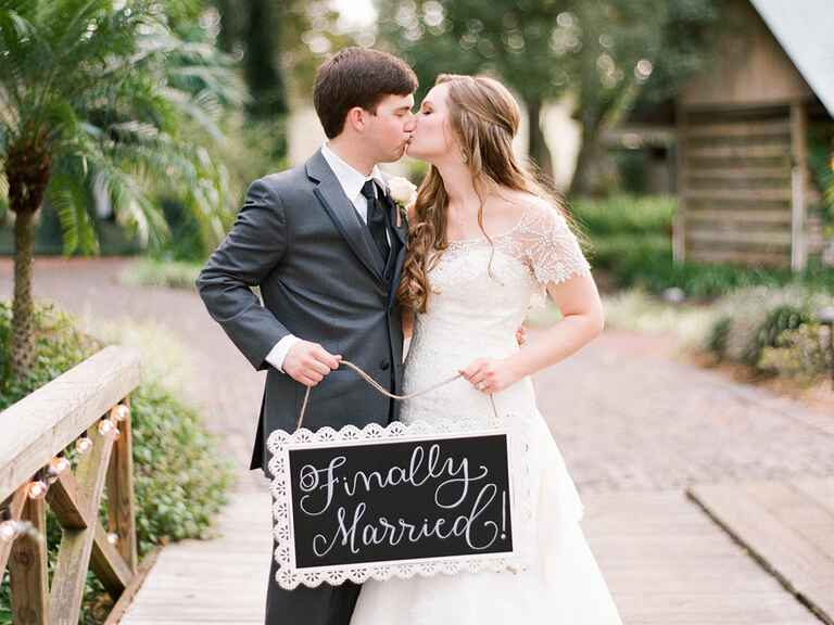 "Bride and groom holding ""finally married"" sign"