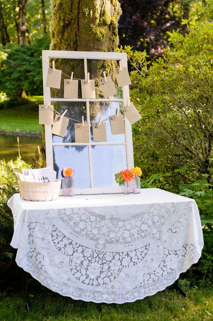 An antique window served as the backdrop for the reception seating chart. Kraft paper cards hung from strings of twine for a rustic touch. A white lace table cloth and reclaimed bottles filled with small bright flowers added an vintage flair.