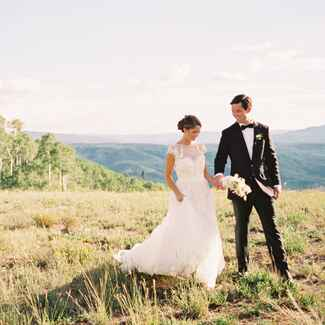 Bride and groom walking on top of mountain