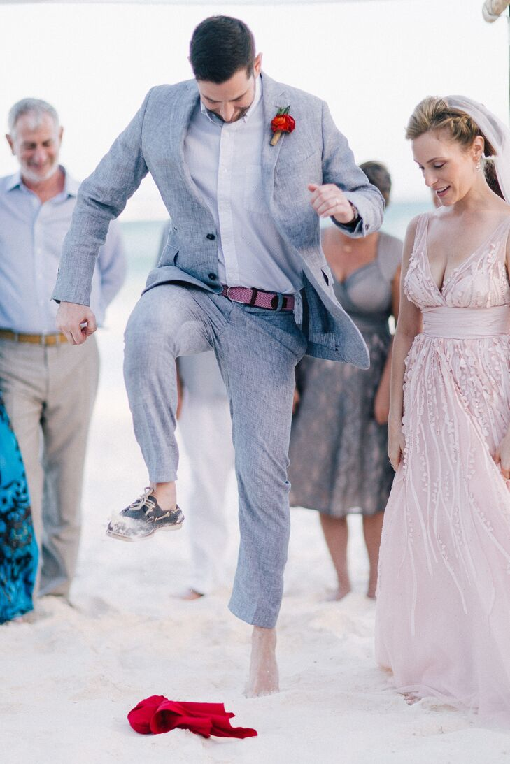 Jason wore a gray linen suit from Louis Purple in New York, with a pink belt and strawberry red boutonniere. He and Danielle participated in the Jewish tradition of breaking the glass to make their marriage official—and they weren't about to let the sand get in their way.