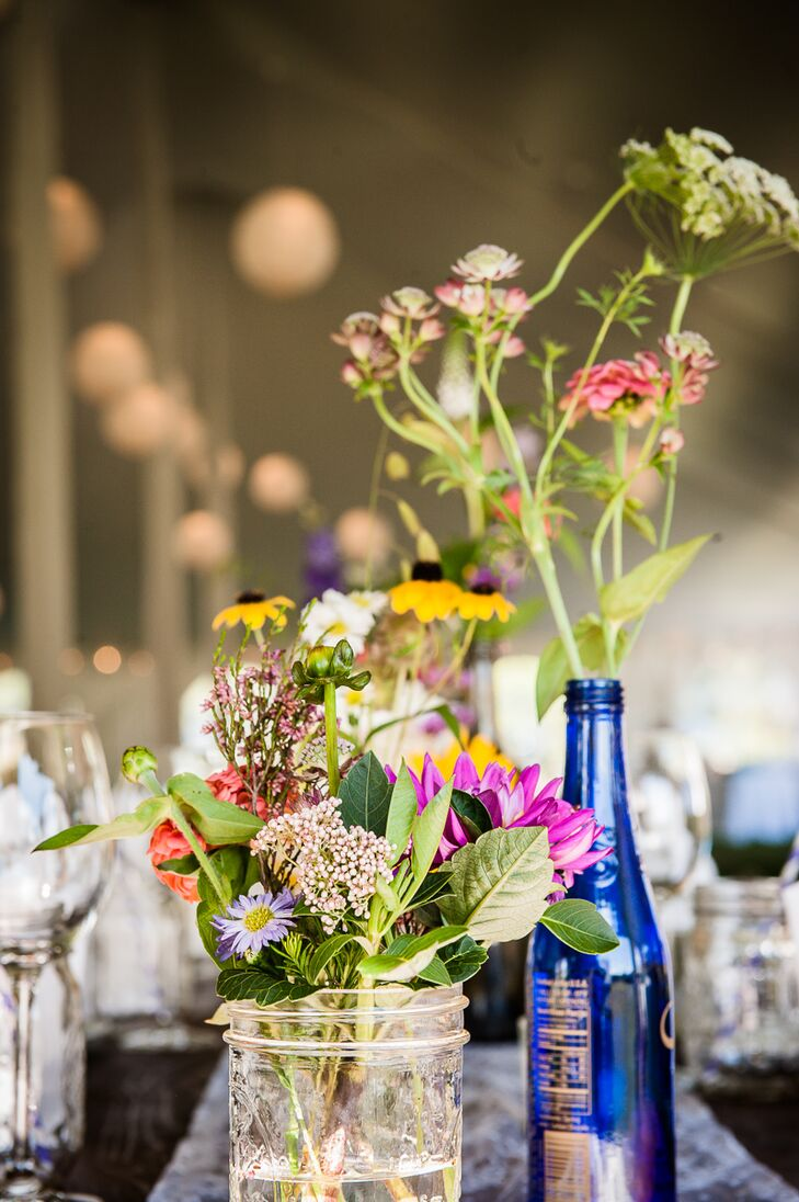 Clusters of various wildflowers placed in vintage glass bottles and vases sat in the center of each farm table.