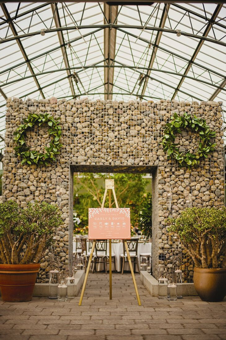 A stone archway decorated with lush green wreaths stood at the entryway to the event. Potted plants and glass hurricane vases with floating candles helped to create a modern Tuscan vibe.