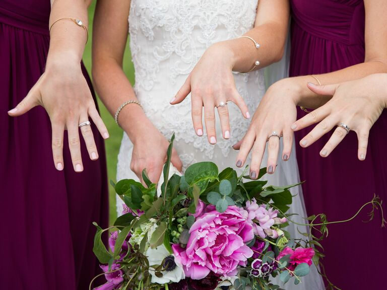 Bride with pale pink nails holding a bright bouquet