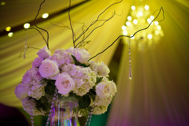 Centerpieces at the reception consisted of flower arrangements with white roses, white hydrangeas and branches. The centerpieces also had dangling crystals that echoed the look of the venue's crystal chandelier.