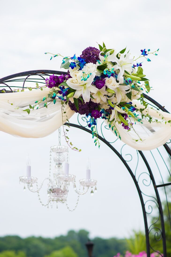 Wedding Arch With Purple and Blue Flowers and a Candelabra