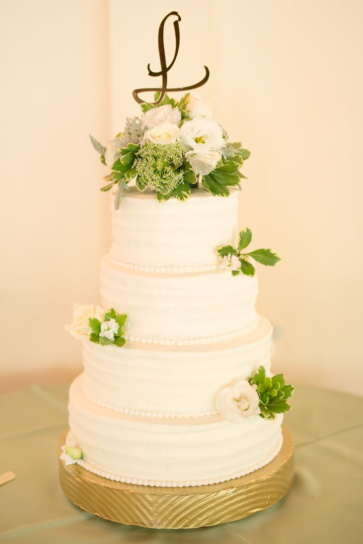 White Four-Tiered Wedding Cake with Fresh Flowers and Greenery