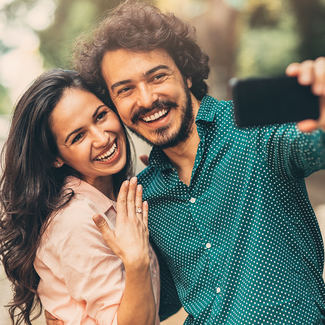Engaged couple posing for selfie