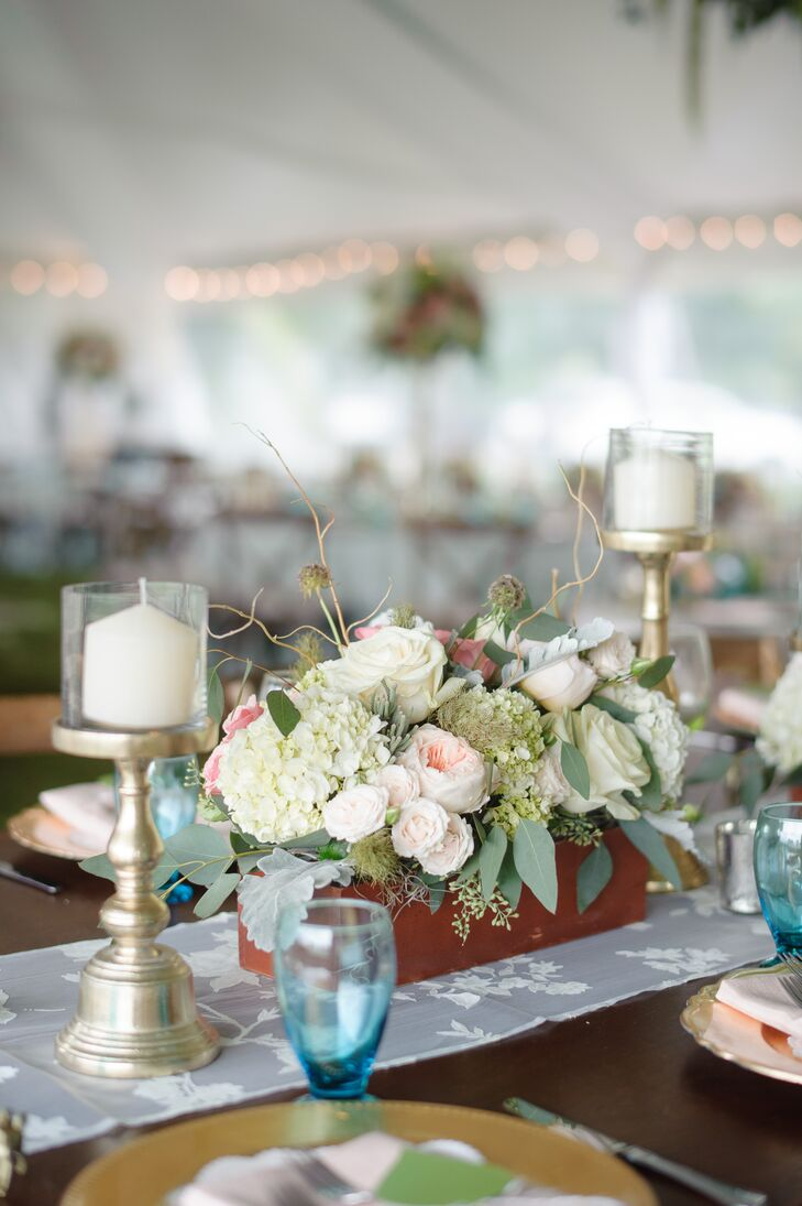 Some family style table had a wooden centerpiece filled with white and green hydrangeas, blush garden roses, white roses and scabiosa pods. Gold candlesticks surrounded the romantic floral decor on each end.
