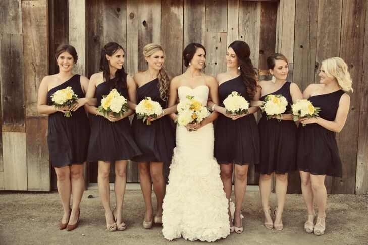 Bridesmaids wore knee-length one-shoulder navy dresses with their bouquets of yellow and white flowers.