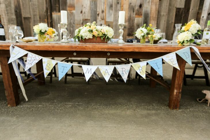 "The head table was decorated with vintage candles and china, wooden planters, romantic floral arrangements and a pennant flag sign that spelled out, ""Just married!"""