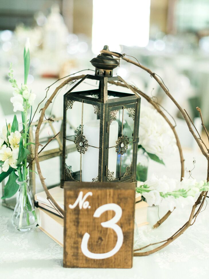 """We created a lot of our own decorations, using pallets for flower boxes and a lighted backdrop for the bar and cake table,"" Ashley says. The centerpieces at the reception were a simple assortment of flowers from the farm, lace, candlelit lanterns and natural twigs to add a sense of rustic ambience."
