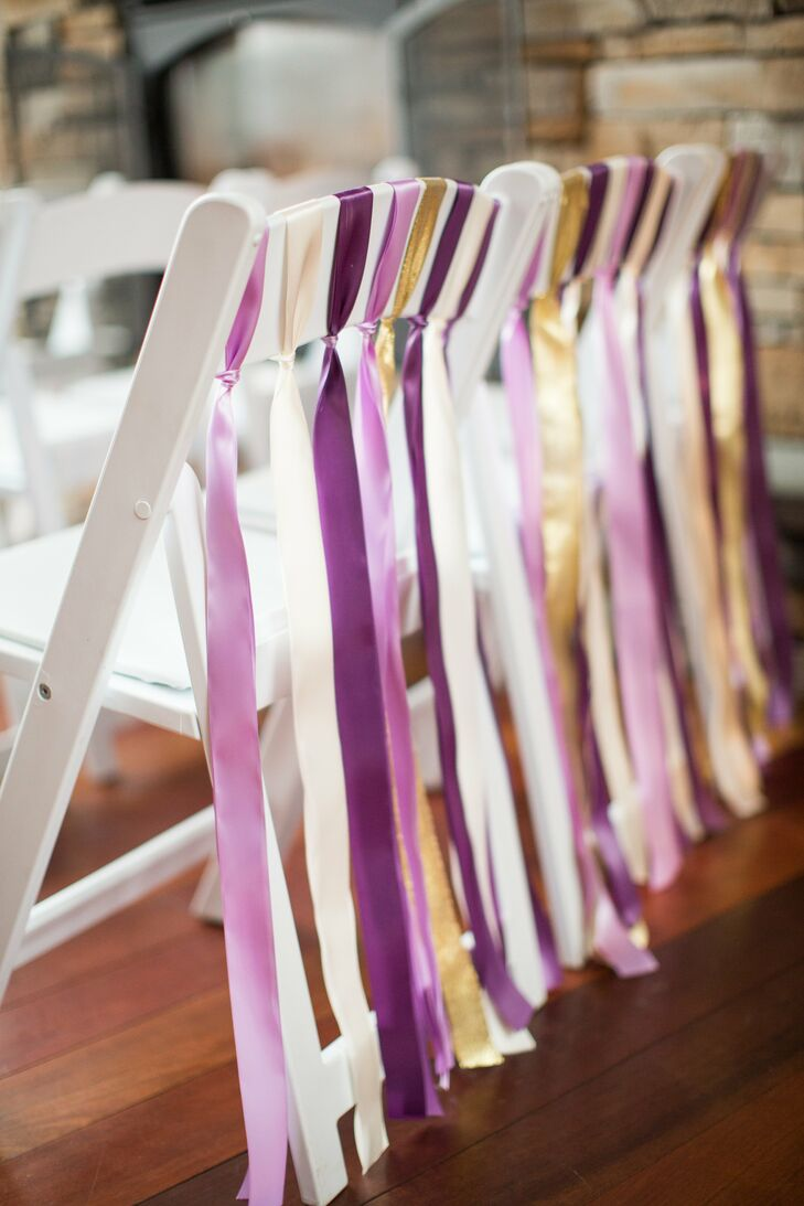 Purple ribbons were tied to the back of the white folding ceremony chairs, giving off a whimsical, romantic vibe.