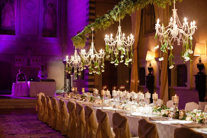 The reception took place in the Conventino Ballroom at Four Seasons Hotel Firenze in Firenze, Italy. The hall was formerly a convent, and it retains many of its architectural and other original details. The space was illuminated by purple uplighting and crystal chandeliers. All of Amanda and Solomon's guests dined at a single long table.