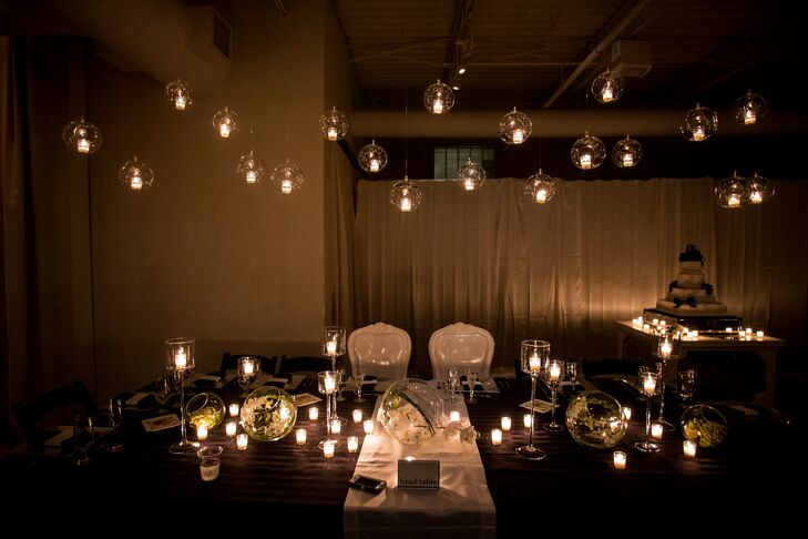 The sweetheart table was decorated with glass bubbles filled with candles hanging from the ceiling.