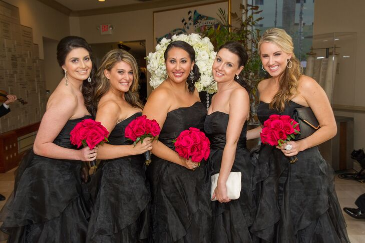 The bridesmaids wore black dresses from David's Bridal  with a sweetheart neckline and elaborate black tulle ruffled detail on the skirt. Each held a bouquet of hot pink roses.
