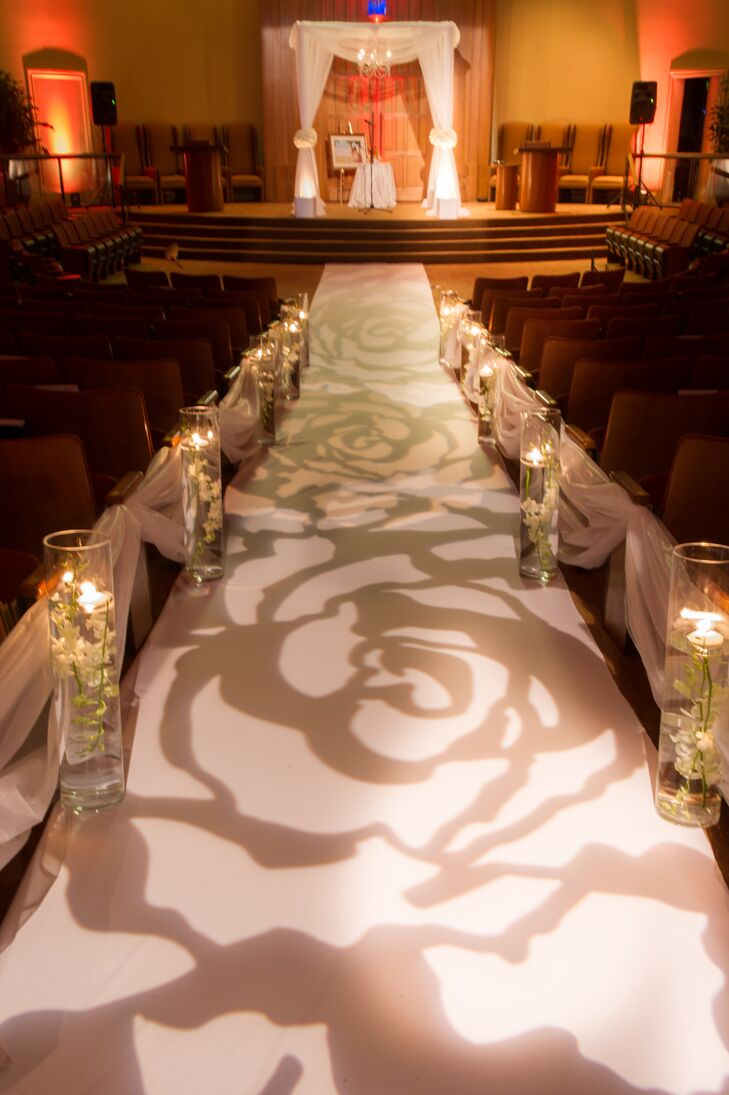 Alina and Rafael decorated their aisle with cylinder vases of floating white cymbidium orchids, draped white fabric and a rose lighting design cascading onto the aisle runner.