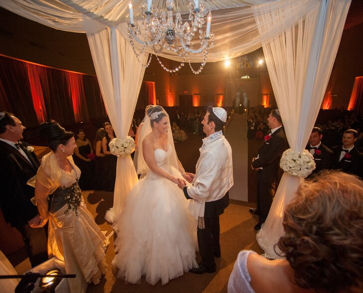 The couple's huppah was decorated with ivory fabric, chandelier lighting and arrangements of white garden roses at each post.