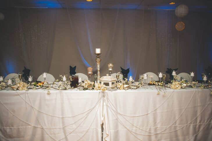 At the reception, dining tables were intricately decorated with a large assortment of flowers, candles, and antique pieces. The tables were also draped in beads.