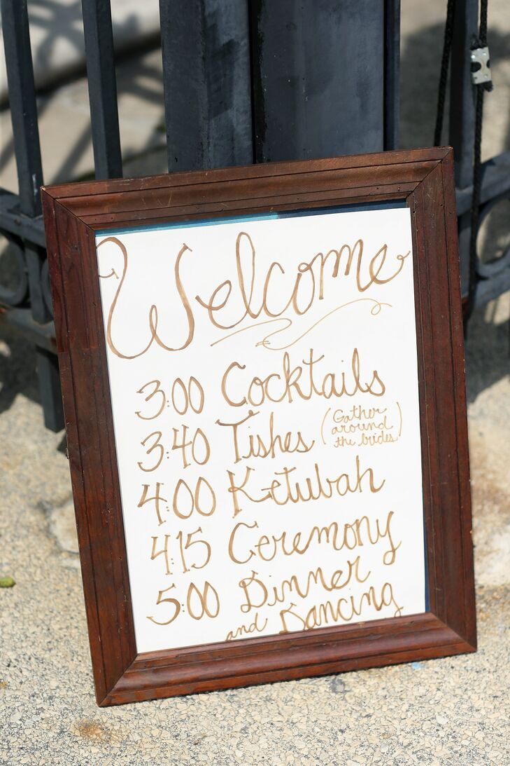 "As everyone entered the wedding, they were welcomed with a sweet handwritten sign. It included every event, from Elana and Jamie's tish (a pre-ceremony celebration) to dinner and dancing. Their first dance in particular was so sweet. ""We told the West Philadelphia Orchestra to play some old jazz, and that is what they did. I am quite indecisive—there are so many great songs—so that's what happened in the end,"" Elana says. ""Looking back, it was perfect. Who knows what song it was? All I remember is dancing with my love, Jamie."""