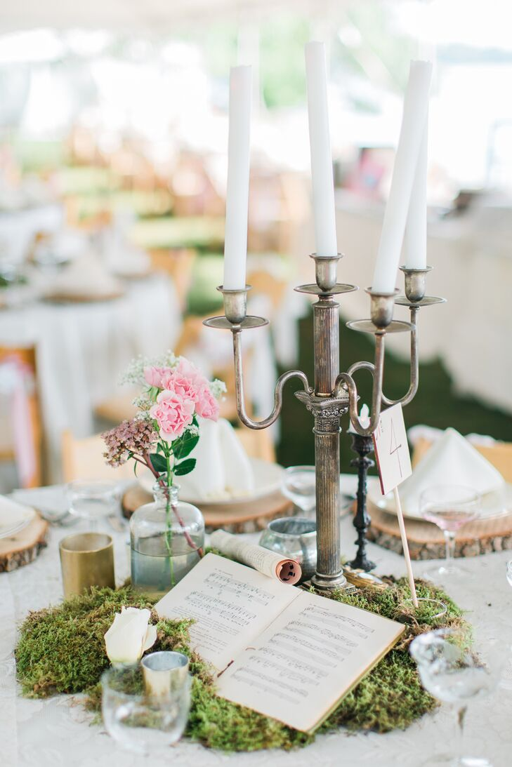 Sliced-wood chargers topped reception tables along with vintage candelabras, sheet music, vintage books and live moss.
