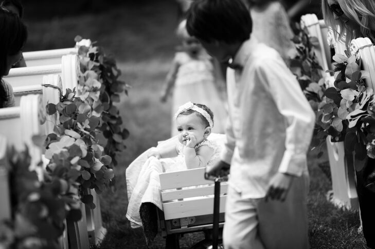 Ring Bearer Pulls Flower Girl Down Aisle in Wagon