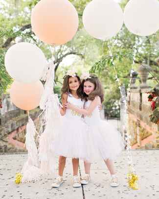Cute flower girl idea with giant tulle skirts and gold Converse sneakers