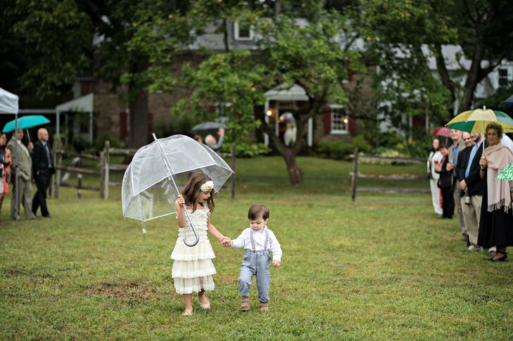 The White Drop-Waist Flower Girl Dress and Suspender-Clad Ring Bearer Under a Bubble Umbrella