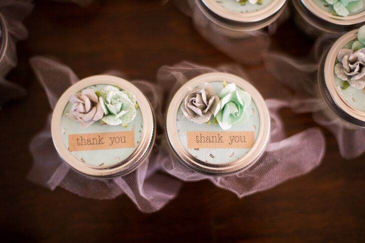 As a way to say thank-you to guests, Denise and James handed out lavender candles placed inside mini mason jars and wrapped with lace and tulle. Paper flowers topped the candle favors, all of which were created by James's mother.