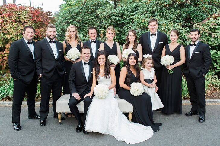 Mariel and Colin's wedding party looked nothing short of timeless in their all-black-and-white ensembles. The bridesmaids stood beside them in chic floor-length dresses by Monique Lhuillier. Each one held a classic white rose and hydrangea bouquet for some added color contrast. Their groomsmen carried on the same hues in formal black, shawl collar tuxedos from Biltmore Tuxedos of Ridgewood, New Jersey. The men paired it with crisp white shirts, black bow ties and black cummerbunds for that classic look.