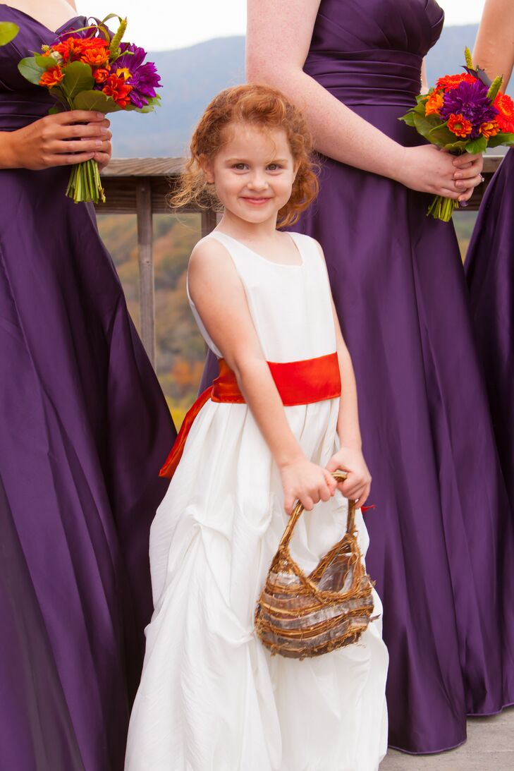 Flower Girl In A White Dress And Red Sash