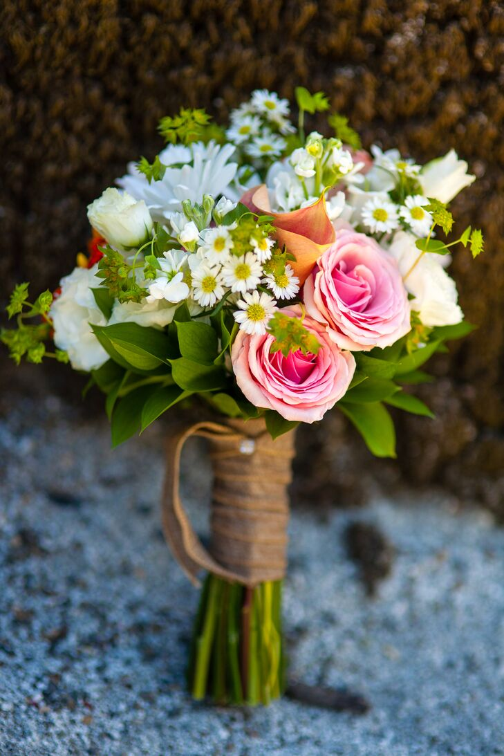 The bride's bouquet was an assortment of white and pink roses, small daisies and accents of green tied together, designed by Bella Vita Event Productions.