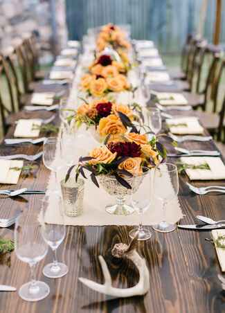 Rustic orange rose centerpieces with antler accents
