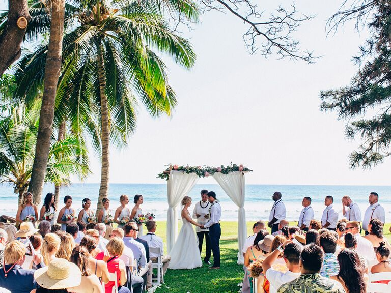 Outdoor wedding in Hawaii with white curtain wedding arch