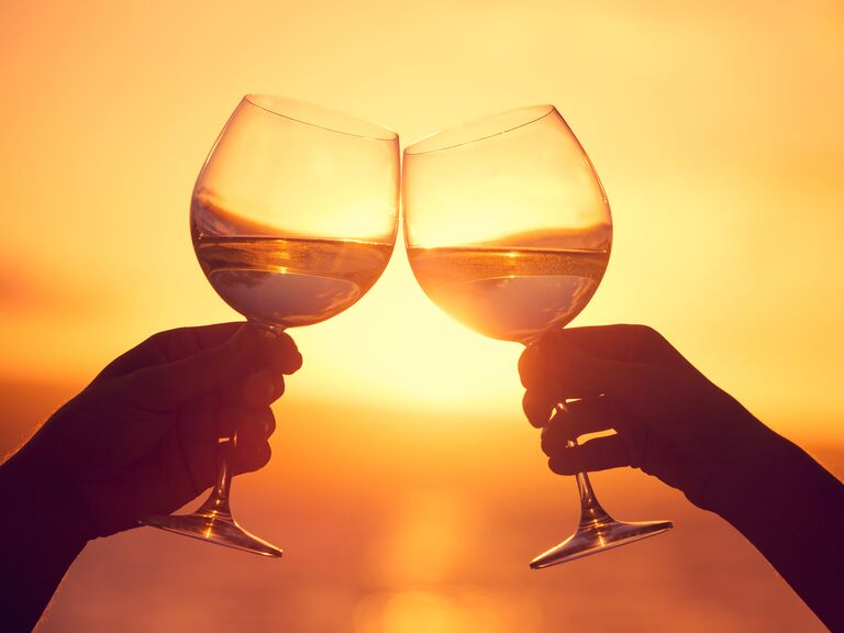Honeymooners toasting on a beach