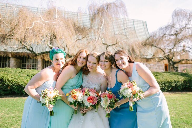 The four bridesmaids wore different dresses in shades of blue and light green that they selected on their own. They carried bright bouquets to offset the cool colors.